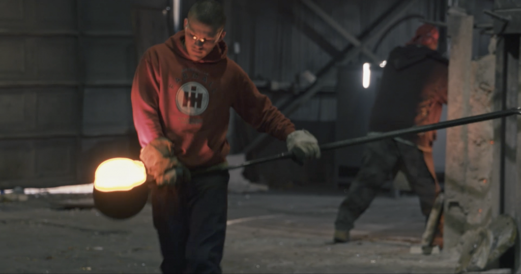 Video still of glass maker with ladle of glass