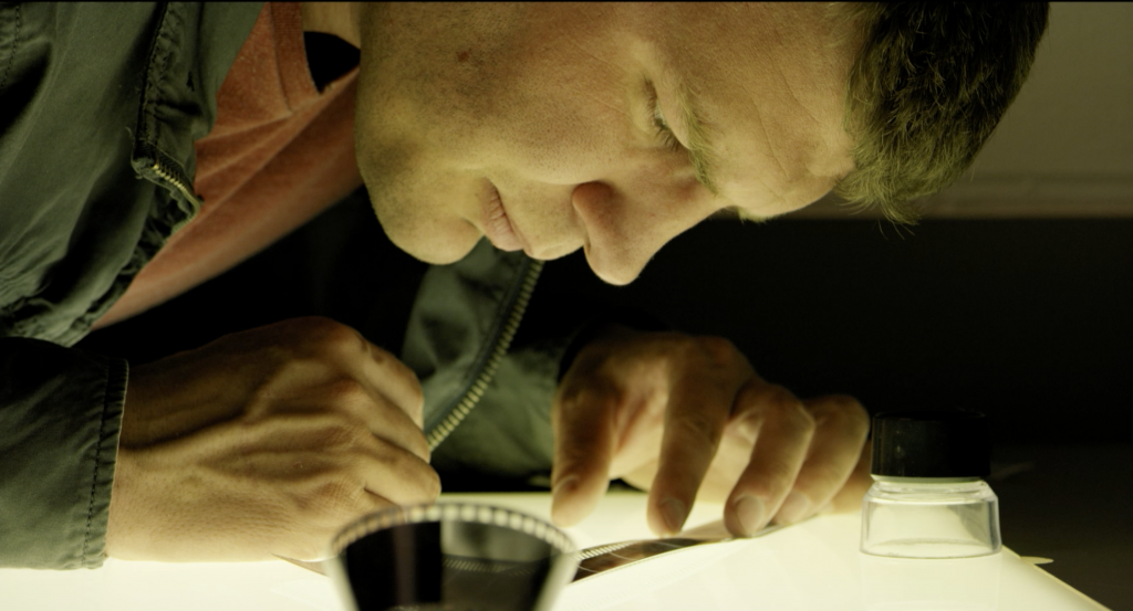 video still of man in darkroom